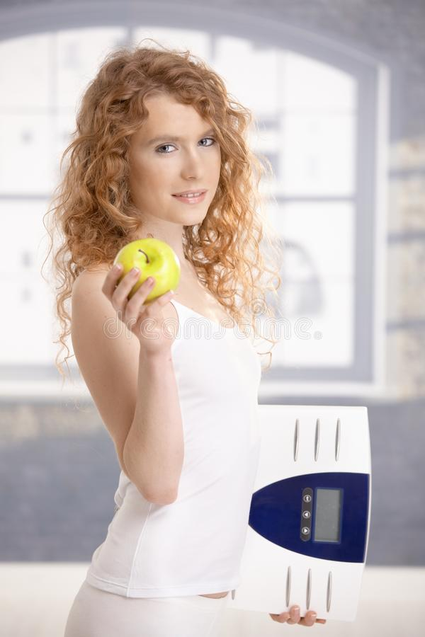 Download Pretty Female Holding Apple And Scale In Hands Stock Photo - Image: 21955540