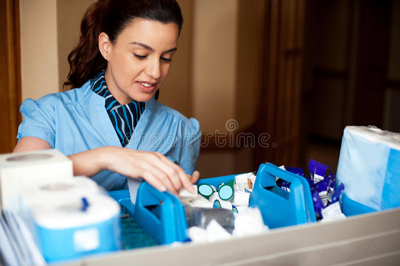 Pretty female housekeeper busy working. Checking and arranging all toiletries in cart stock photography