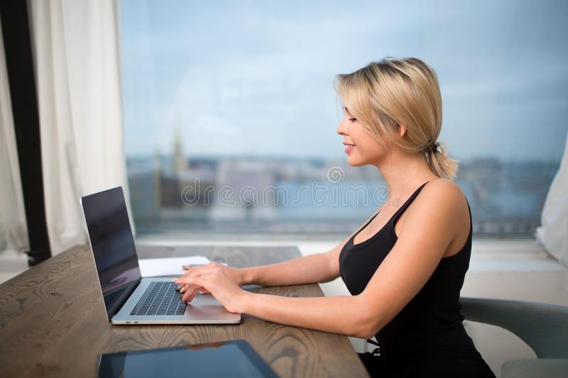 Pretty female magazine editor keyboarding on net-book. Financier using notebook for chat. Smiling woman publication specialist typing text on modern laptop stock photography