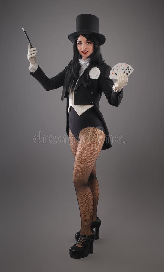 Female magician in performer suit with magic wand and playing ca stock images
