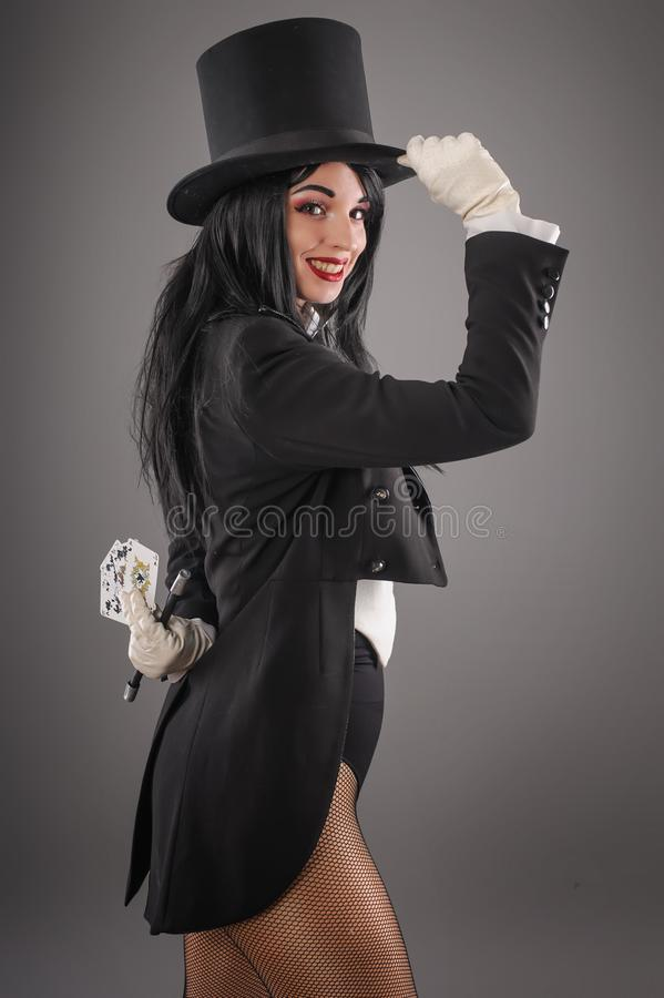 Female magician in performer suit with magic wand and playing ca royalty free stock photography
