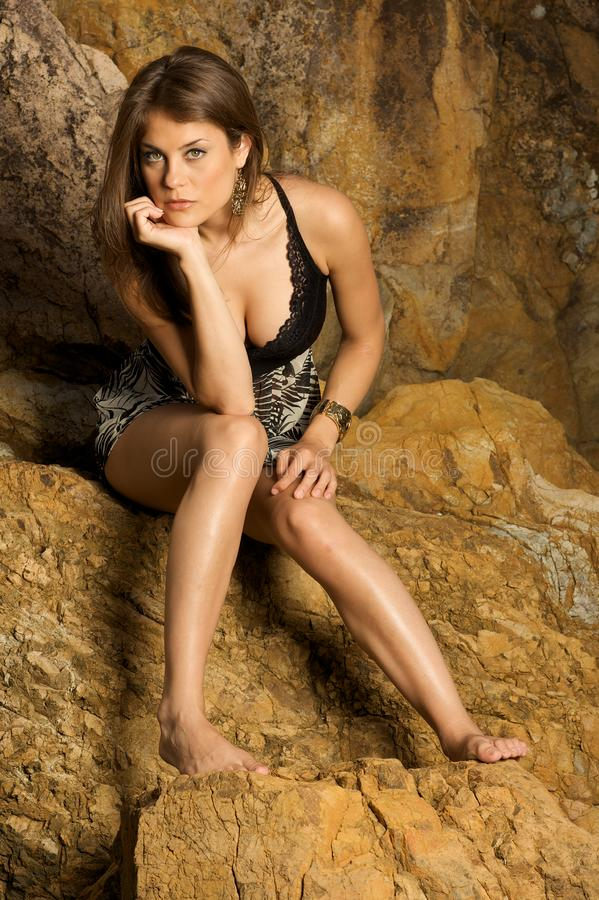 Pretty female model sitting on the rocks royalty free stock photo