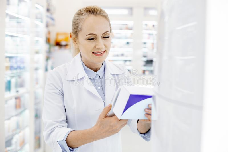 Pretty female pharmacist identifying pills. Drug interaction. Beautiful female pharmacist using tablet while holding medication royalty free stock photo