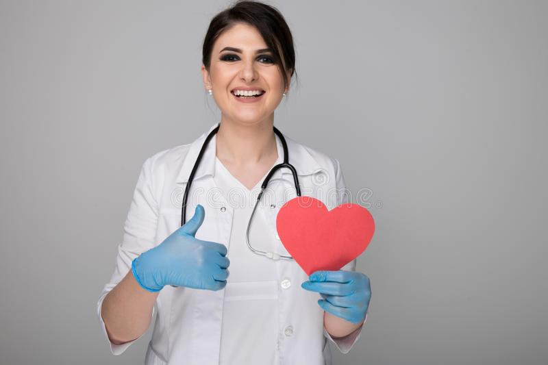 Pretty female physician with stethoscope and image of heart showing thumb isolated over the grey background. stock images