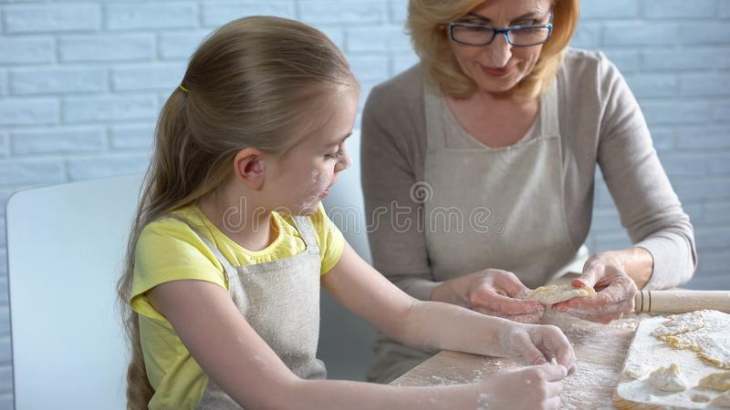 Pretty female preschooler trying to cook pastry, helping her granny in kitchen stock images