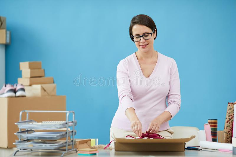 Pretty female in pullover tying knot on top of parcel for client of online shop stock photo