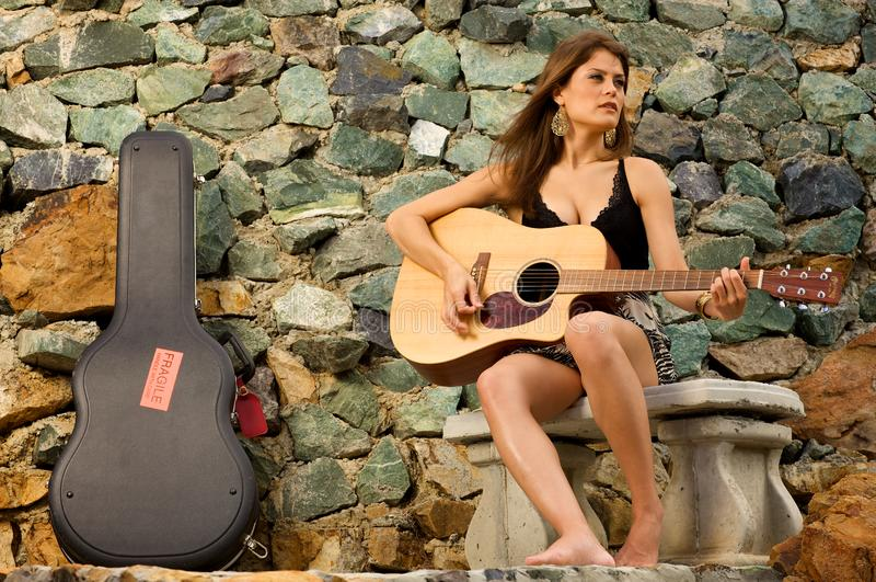 Pretty female singer playing guitar. royalty free stock photography