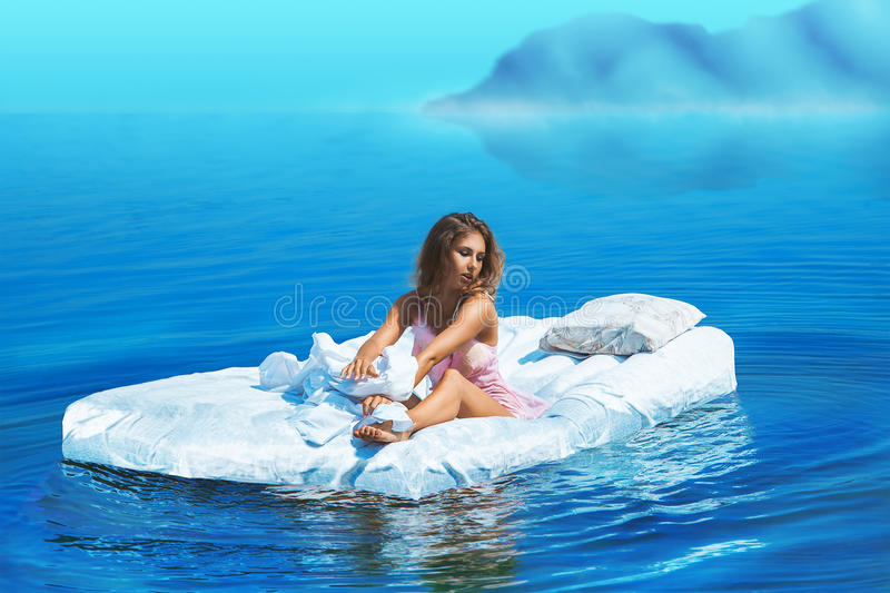 Pretty female sit on bed in lake. At daylights stock photography