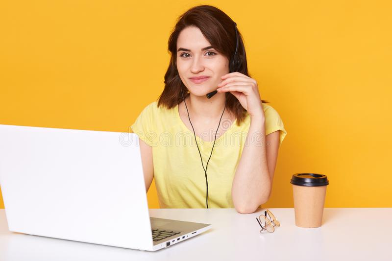 Pretty female sits at white desk with opened laptop computer, writes email, uses high speed internet, poses isolated over yellow stock image