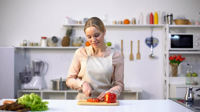 Pretty female slicing red bell pepper, cooking salad for dinner, raw food diet stock image