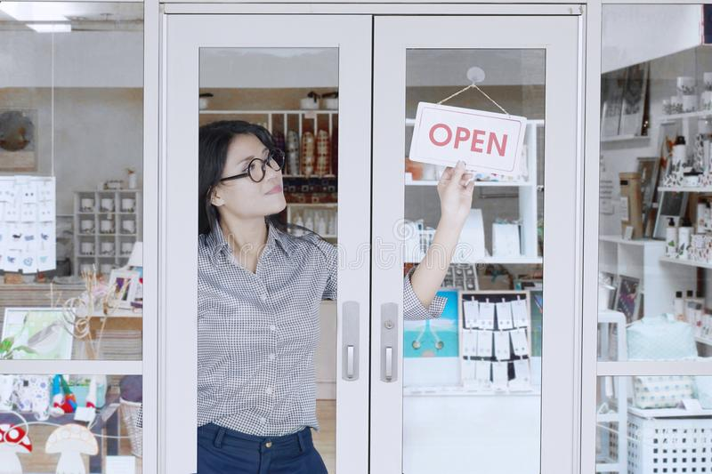 Store owner turning open sign. Pretty female store owner turning open sign on the doorway at her souvenir store royalty free stock image