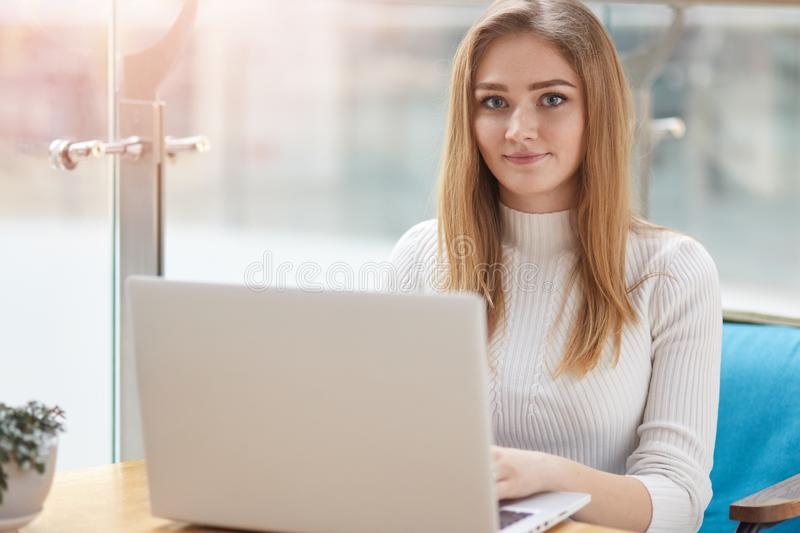 Pretty female student with cute smile prepares for test in cafe. Beautiful happy woman works on laptop computer during coffee. Break in cafe bar. Blonde wears stock image