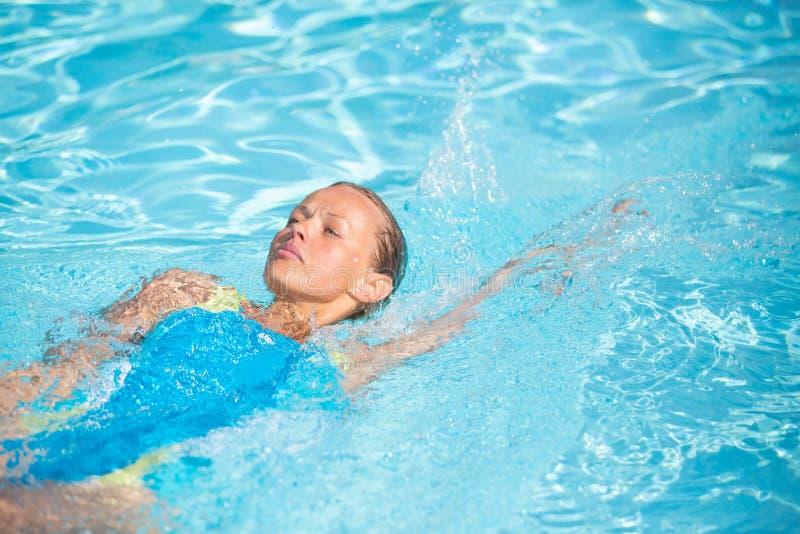 Pretty female swimmer in a pool stock photo