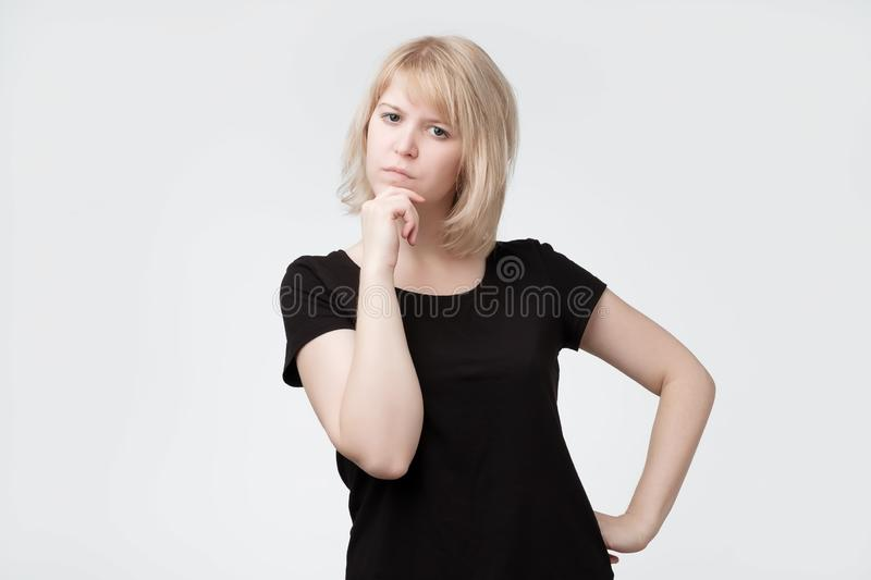 Pretty female teenager thinking, holding finger at her mouth, looking at camera. Isolated on white studio background stock image
