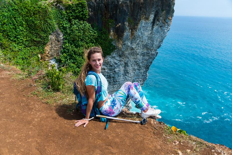 Pretty female traveler with a backpack sitting on the edge of a cliff and smiling on camera. Bali, Indonesia stock image