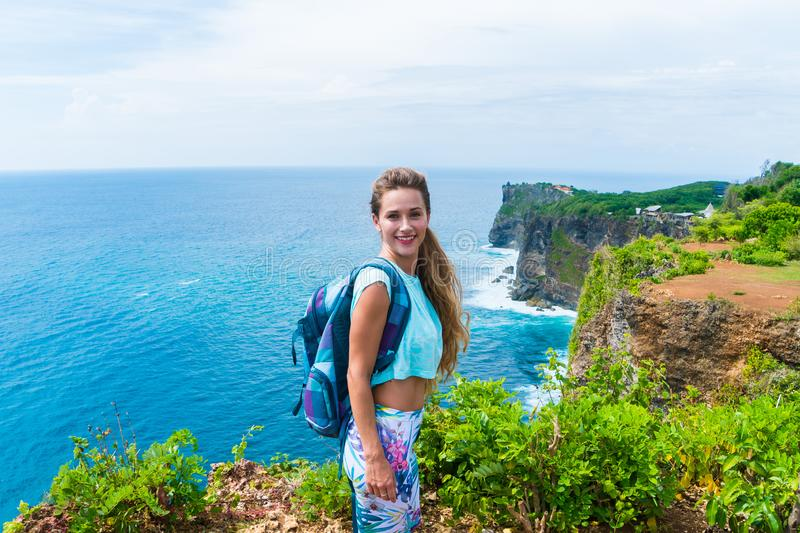 Pretty female traveler with a backpack standing on the edge of a cliff and smiling on camera. Bali, Indonesia royalty free stock images