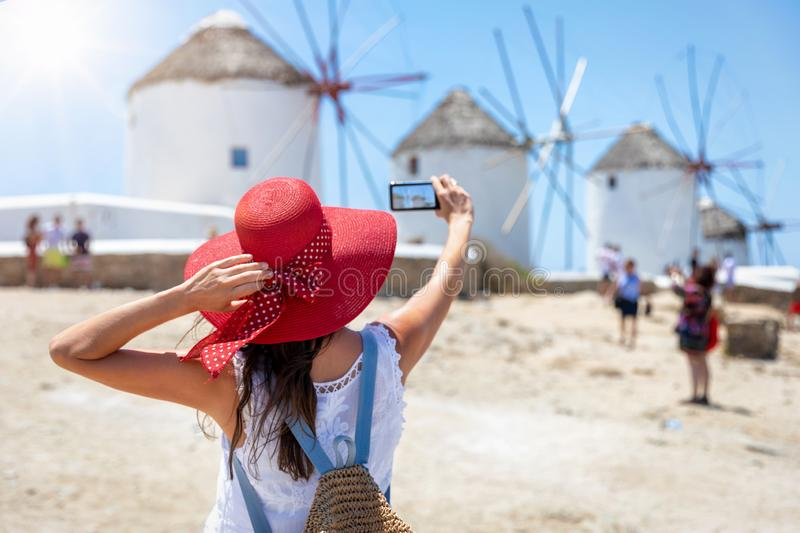 Female traveler takes pictures of the famous windmills, Mykonos island, Cyclades, Greece stock images