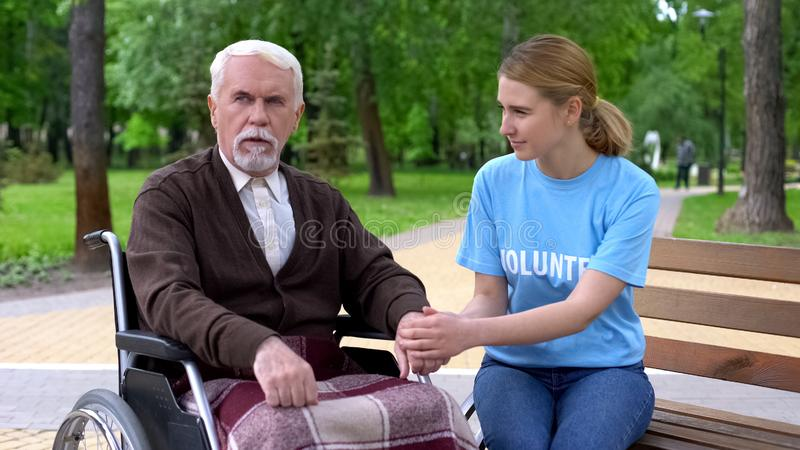 Pretty female volunteer supporting aged male patient in wheelchair, assistance royalty free stock photos