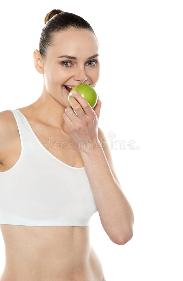 Download Pretty Fit Trendy Woman Eating Fresh Green Apple Stock Photo - Image: 26097584