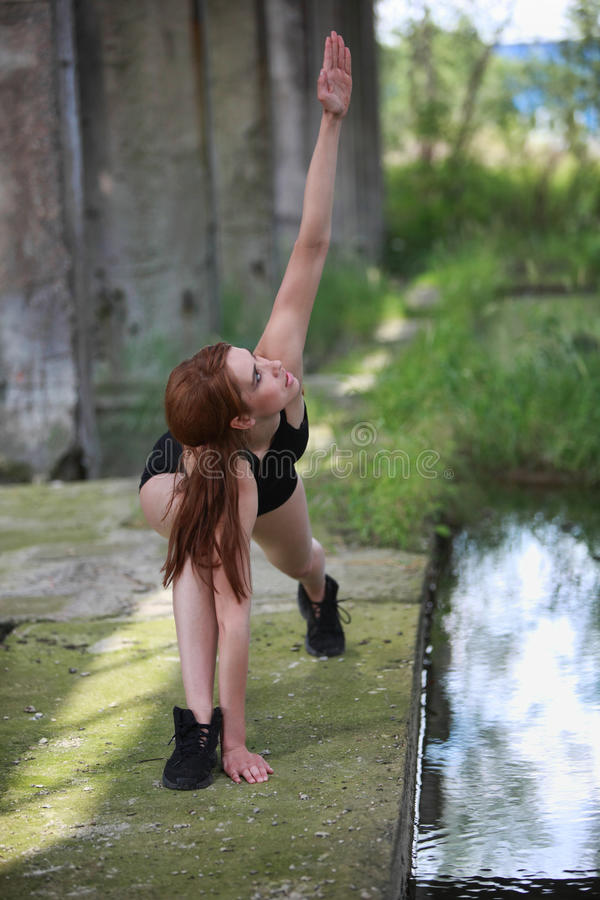 Pretty fit woman exercising in black gymnastic outfit royalty free stock photo