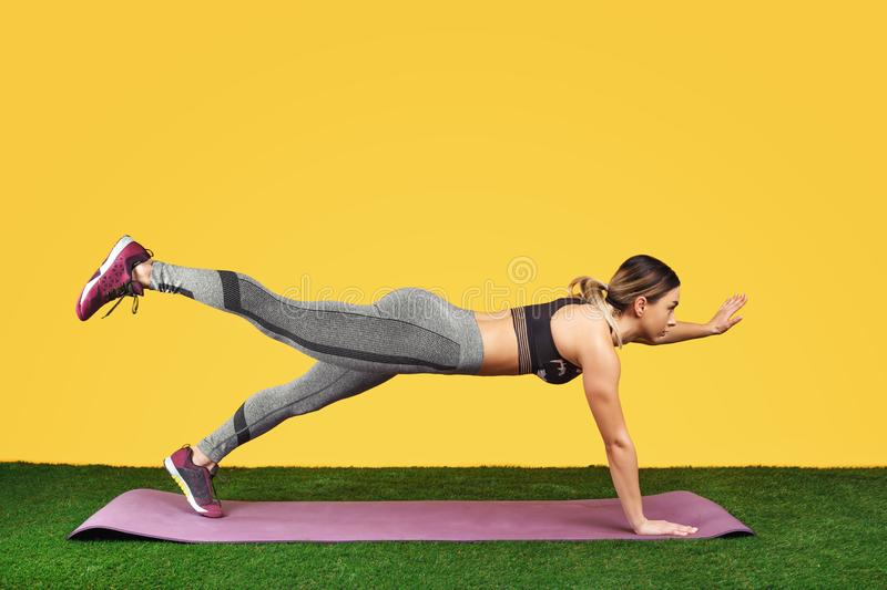 Pretty fit young woman do exercise on the fitness purple mat on green grass over yellow background. Pretty fit young woman do exercise on the fitness purple mat royalty free stock photography