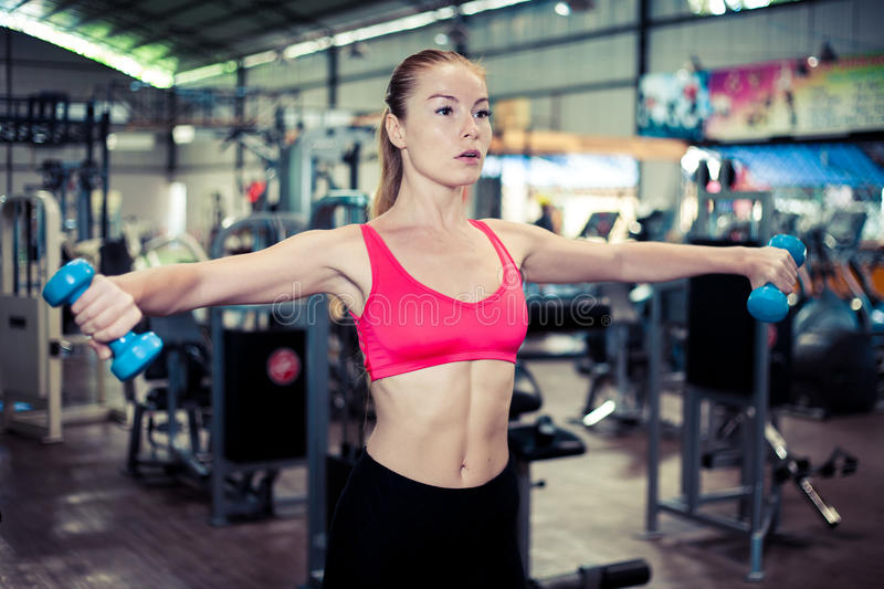Pretty fitness girl with dumbbells. Attractive woman in gym. stock images
