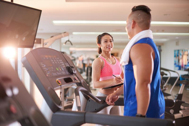 Fit man meeting trainer in gym royalty free stock photography