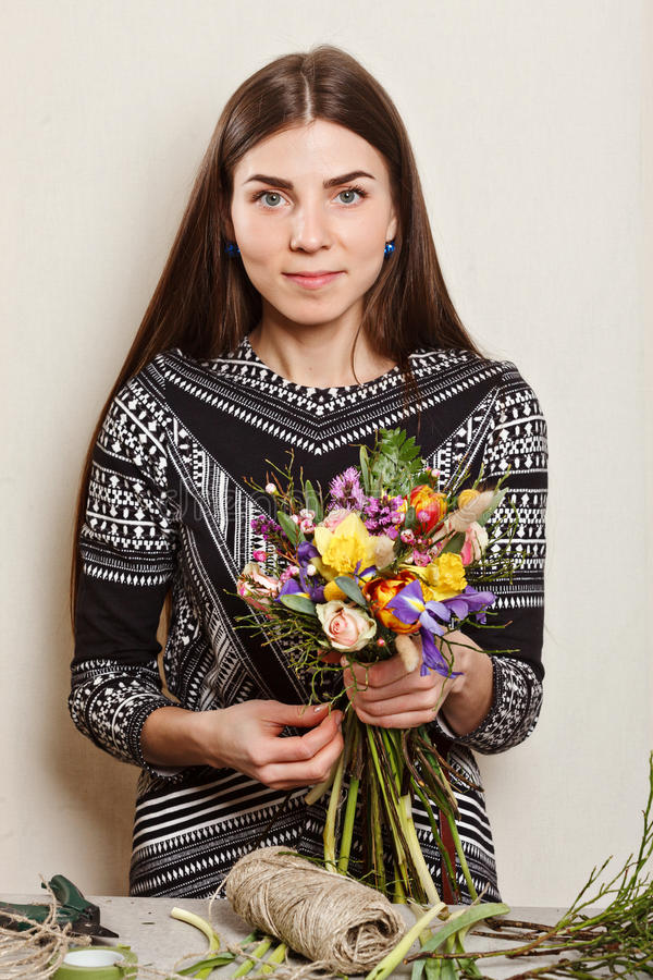 Pretty florist making bouquet from spring flowers royalty free stock photo