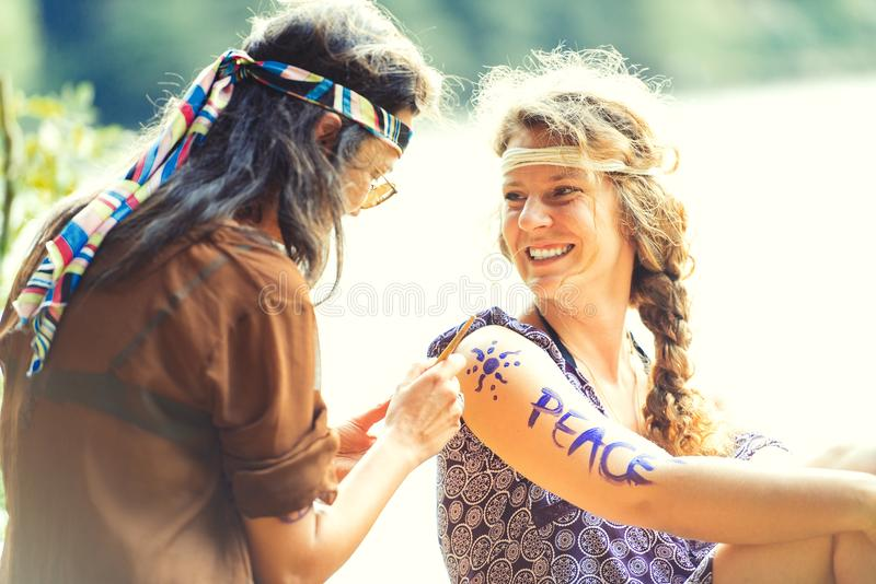 Pretty free hippie girls. Body painting - Vintage effect photo. Pretty free hippie girls. Body painting. Outdoor in peace and free love. Top view - Vintage stock images