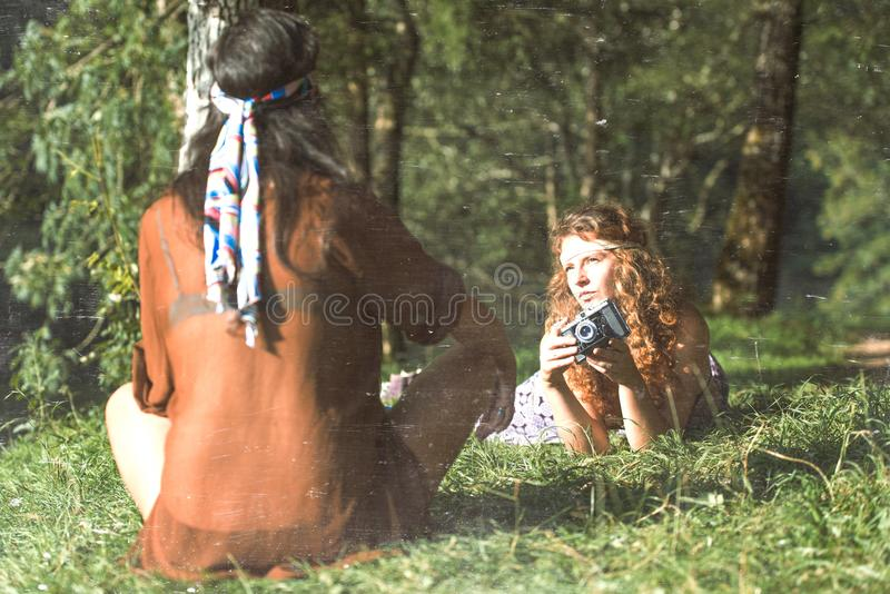 Pretty free hippie girls on the grass taking photos with an old. Camera. Outdoor in peace and free love. Top view - Vintage effect photo royalty free stock photography