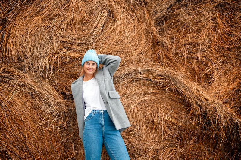 Pretty fresh darkhaired young woman. Walking outdoors in the sun against the background of haystacks and wearing a coat, knitting hat, jeans.Concept of autumn royalty free stock photos