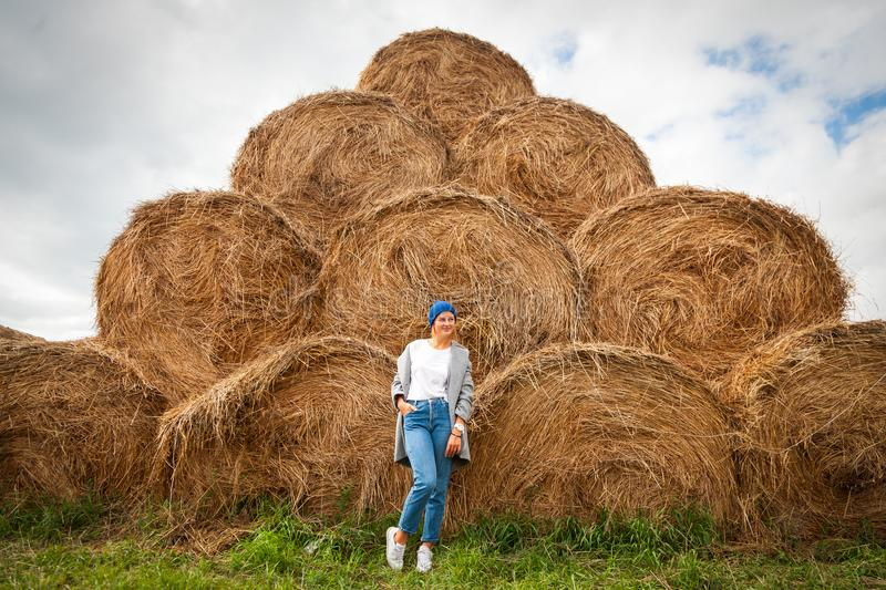 Pretty fresh darkhaired young woman. Walking outdoors in the sun against the background of haystacks and wearing a coat, knitting hat, jeans.Concept of autumn royalty free stock photo