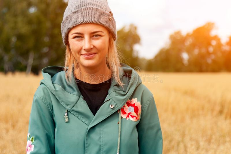 Pretty fresh darkhaired young woman. Walking outdoors in the sun and high grass field and wearing a coat, knitting hat, jeans.Concept of autumn holidays at royalty free stock image
