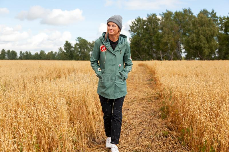Pretty fresh darkhaired young woman. Walking outdoors in the sun and high grass field and wearing a coat, knitting hat, jeans. Concept of autumn holidays at royalty free stock image