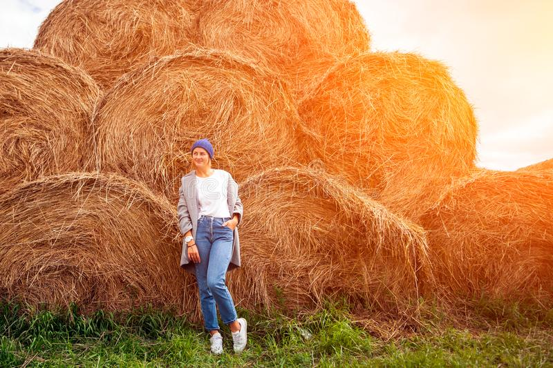 Young beautiful darkhaired woman. Pretty fresh darkhaired young woman walking outdoors in the sun against the background of haystacks and wearing a coat royalty free stock photo