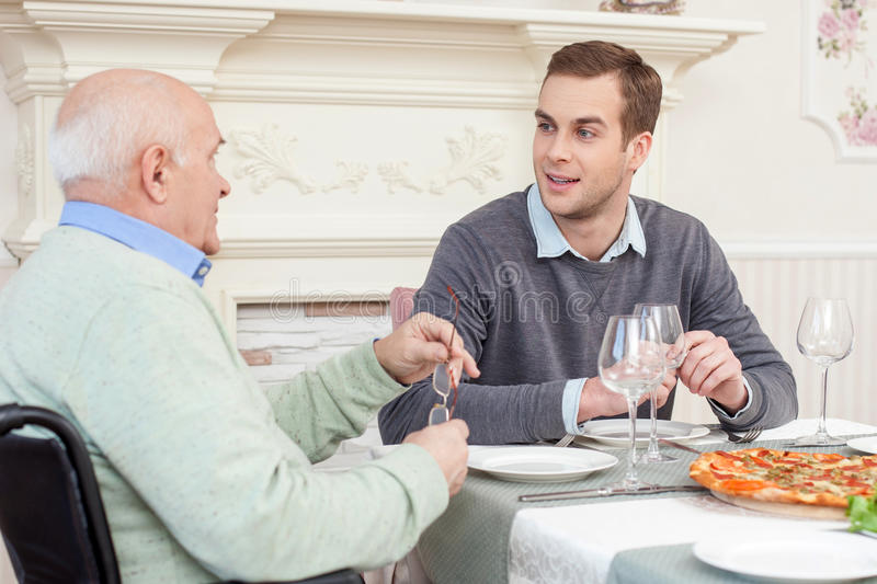 Pretty friendly family has a lunch at home. Mature father and his son are dining together. They are talking and smiling. The old men is sitting on wheelchair at stock image