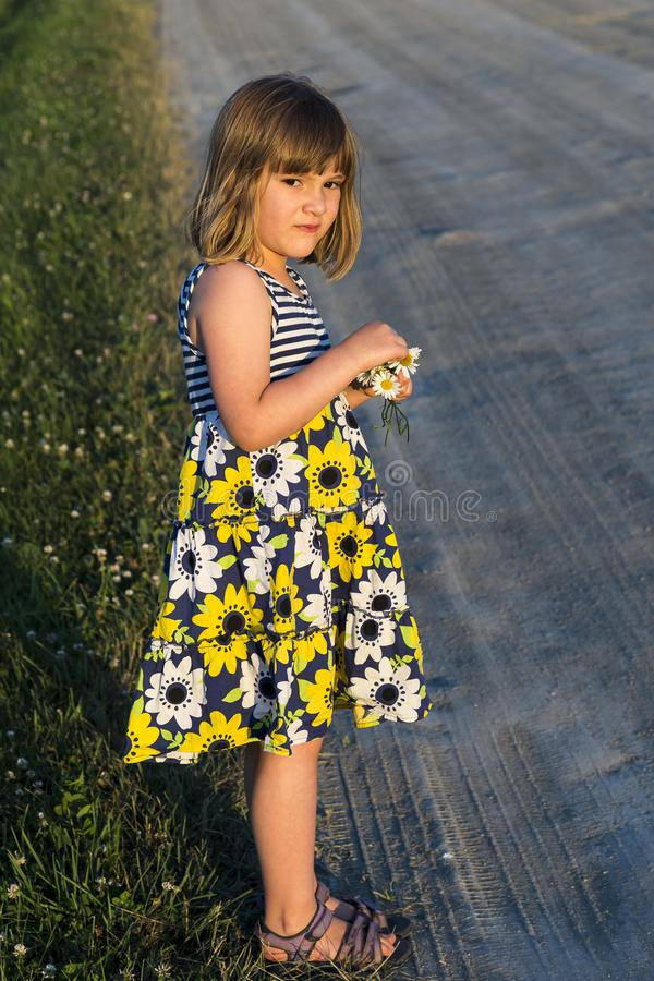 Pretty frowning little girl in summer dress standing next to a dirt road stock images