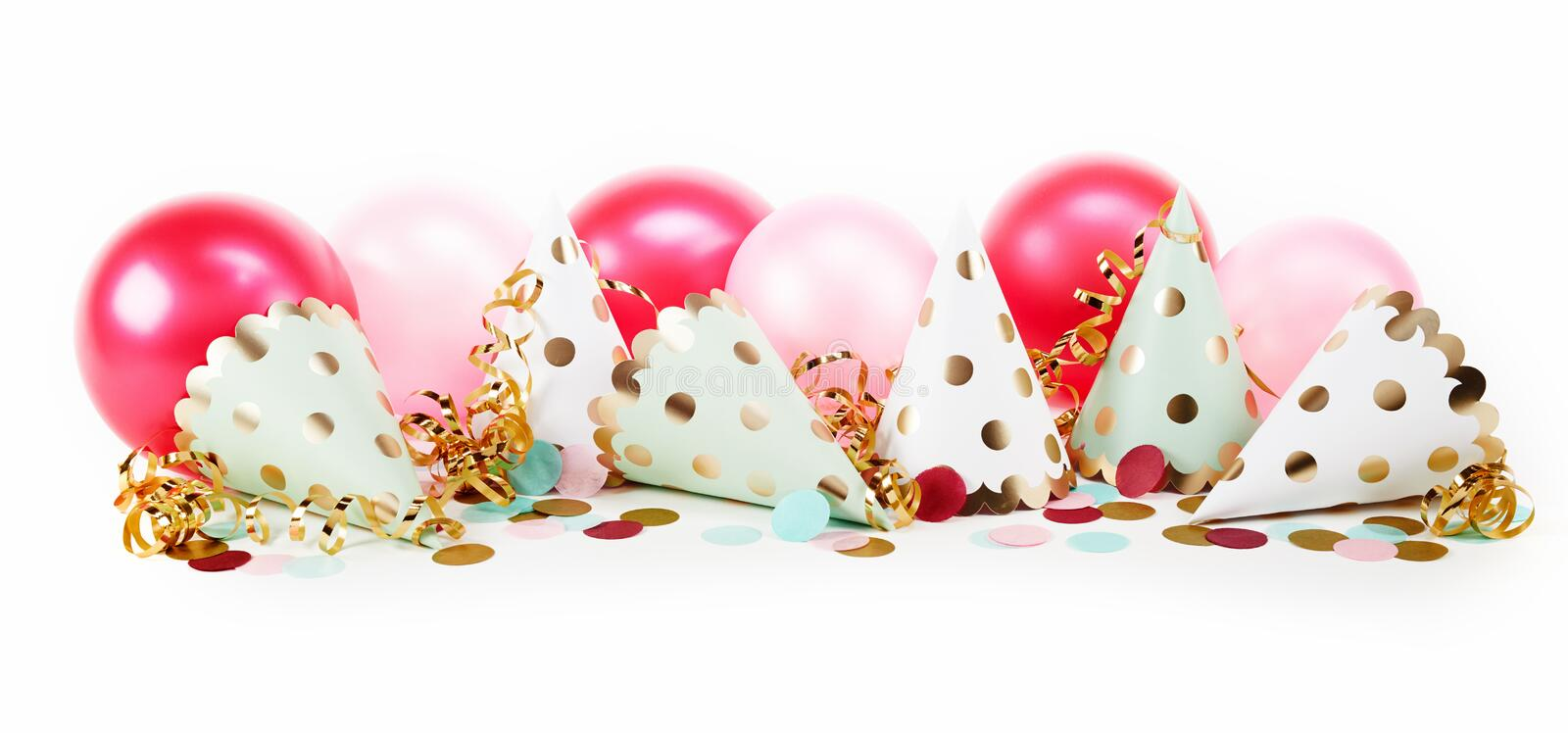 Pretty fun polka dot carnival banner. With gold and white party hats, confetti and pink balloons on white stock photos