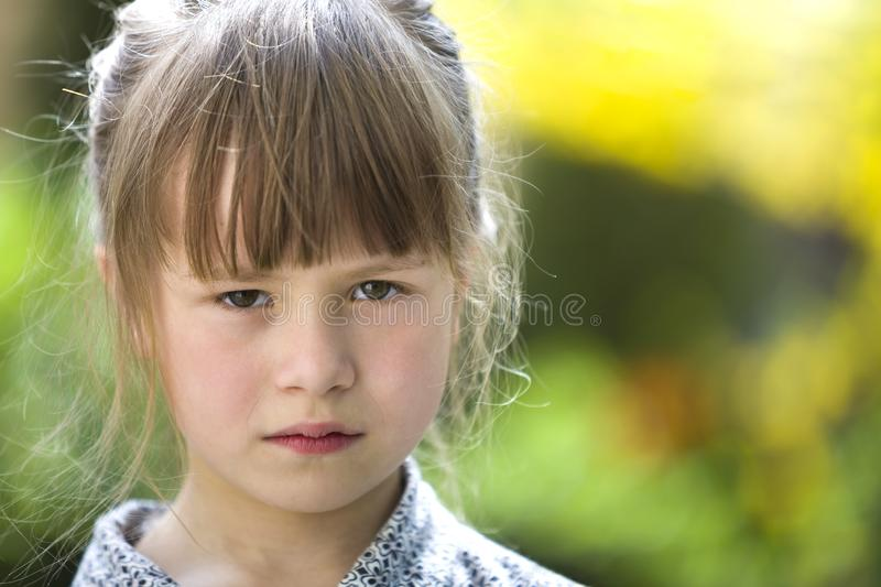 Pretty funny moody young child girl outdoor feeling angry and unsatisfied on blurred summer green background. Children tantrum. Concept stock photo