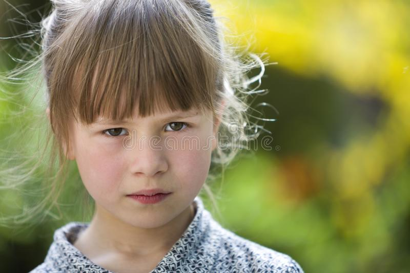 Pretty funny moody young child girl outdoor feeling angry and unsatisfied on blurred summer green background. Children tantrum. Concept stock image