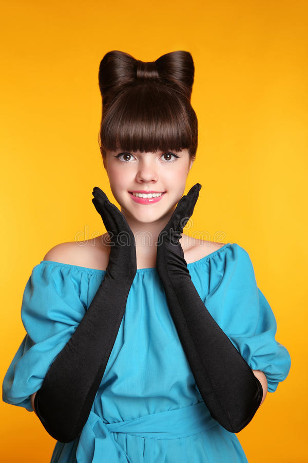 Pretty funny smiling girl beauty portrait. Elegant Fashion Glamorous teen Model wearing black Glamour Gloves. Bow Hairstyle and M royalty free stock photos