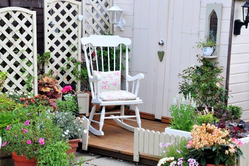 Pretty garden area. A pretty garden area with rocking chair royalty free stock photos
