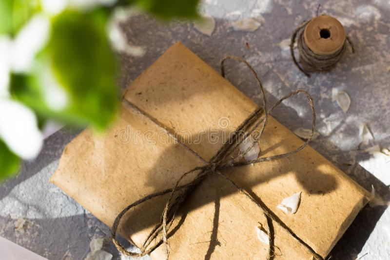 Pretty gift box wrapped with brown craft paper and decorated with jute stock photo