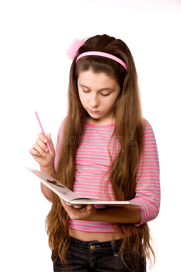 Pretty girl in the age of eleven reading book stock photos