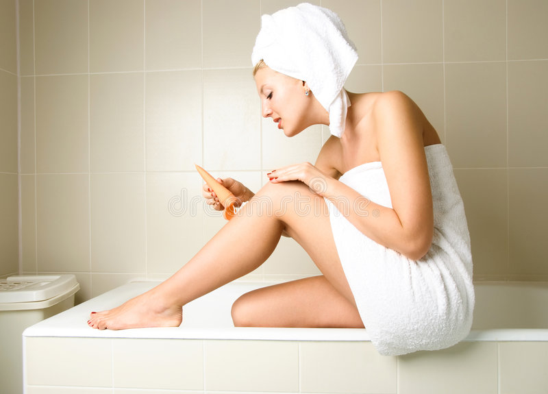 Pretty girl applying body lotion stock images