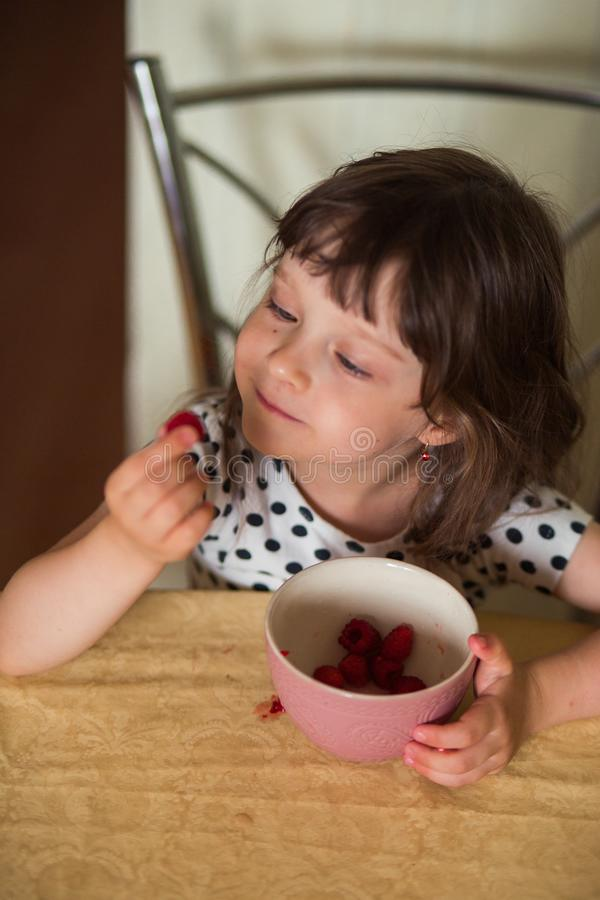 A pretty girl with bangs in a white polka-dot dress looks at a delicious raspberry berry. vertical photography royalty free stock photography