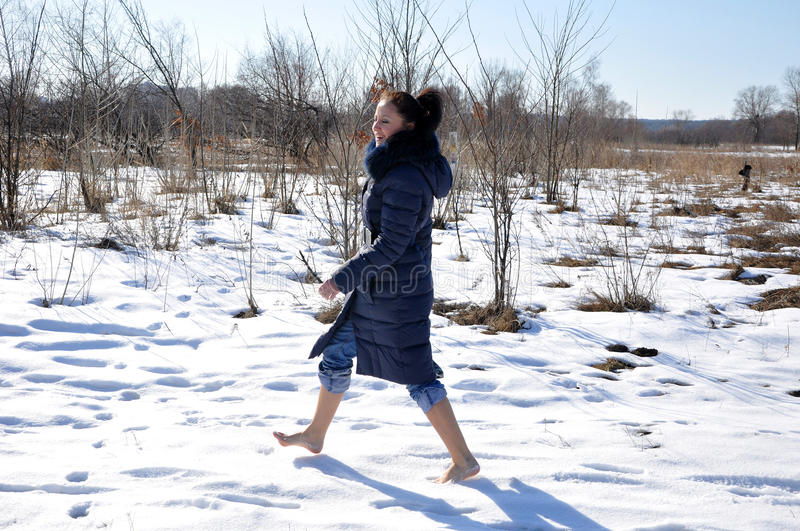 Pretty girl barefoot walking on snow stock photos