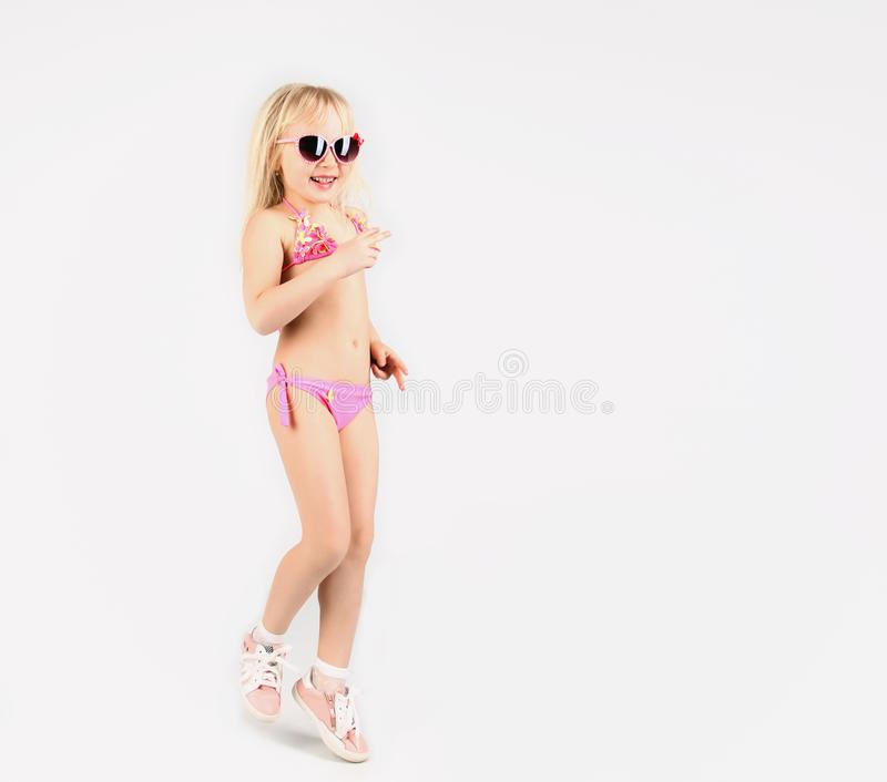 Pretty girl in bathing suit and glasses, having fun dancing and. Showing emotions, on white background, soft focus stock images
