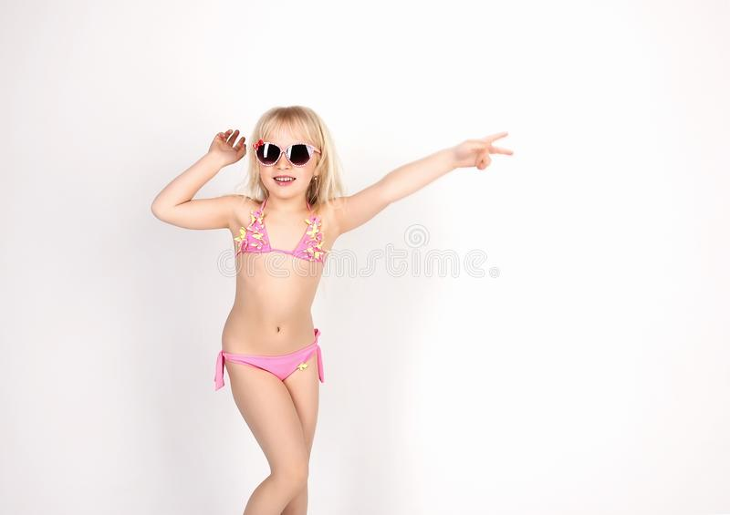 Pretty girl in bathing suit and glasses, having fun dancing and. Showing emotions, on white background, soft focus stock photo