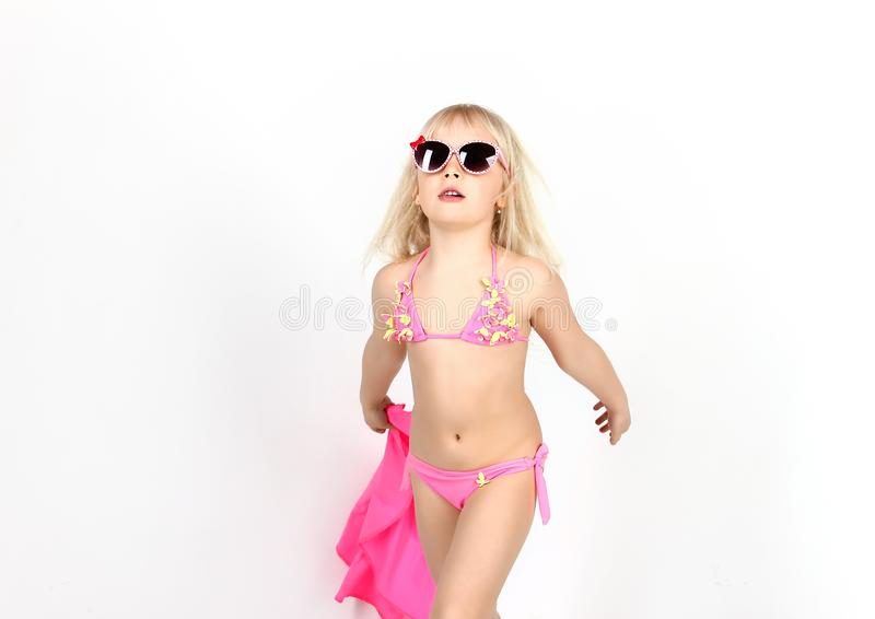 Pretty girl in bathing suit and glasses, having fun dancing and. Showing emotions, on white background, soft focus stock image